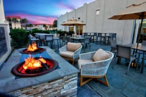 outdoor patio at night with fire pits burning at sunset