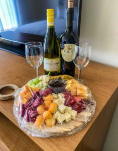in room enhancements, bottles of wine and a fruit and cheese tray